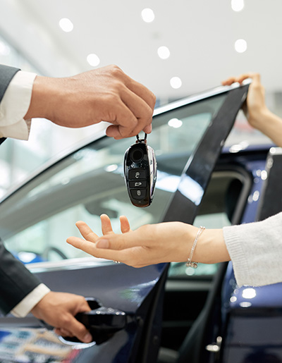 Cropped image of young woman receiving keys from her new car